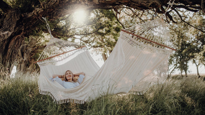 Hier ist eine Frau zu sehen, die in einer Hängematte entspannt